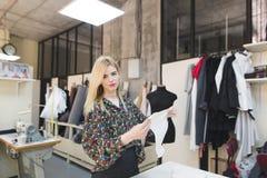 A costureira bonita está em um estúdio com um pano branco em seus mãos e olhares na câmera foto de stock