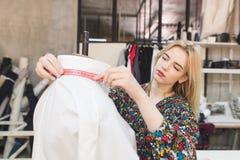 A costureira bonito mede o comprimento de uma roleta em um manequim ao trabalhar em um estúdio imagens de stock royalty free