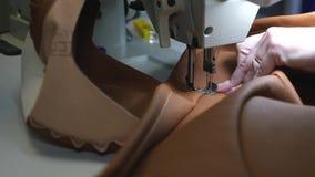 A costureira costura em uma oficina costurando o alfaiate costura o couro marrom em uma oficina costurando agulha da máquina de c vídeos de arquivo