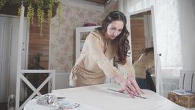 A costureira da mulher mede o comprimento desejado o da tela video estoque