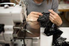 A costureira da mulher trabalha com laço na oficina Fotos de Stock