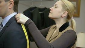 Costureira loura que mede um homem de negócios para um terno ou a fim alterar esse que está vestindo vídeos de arquivo