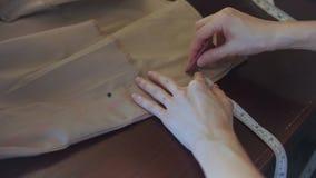 A costureira marca um teste padrão na tela bege filme