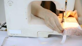 Costureira na máquina de costura que rabisca a parte de tela cor-de-rosa filme