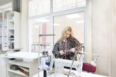 A costureira nova da costureira está no local de trabalho, trabalha e fala em um telefone celular foto de stock royalty free