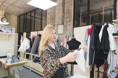 A costureira nova está em um estúdio com um pano em suas mãos A costureira olha o tkinin em suas mãos foto de stock