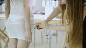 A costureira toma medidas com a mulher para costurar a roupa no estúdio video estoque