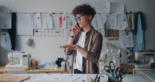 Costureiros fêmeas que falam no telefone celular que olha os esboços que trabalham no estúdio vídeos de arquivo