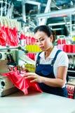 Costurera china en una fábrica de la materia textil Foto de archivo libre de regalías