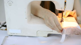 Costurera en pedazo de garabateo de la máquina de coser de tela rosada