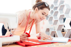 Costurera feliz de la mujer en el trabajo con la tela roja Imagenes de archivo