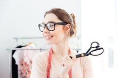 Costurera feliz de la mujer que sonríe y que sostiene las tijeras en estudio del diseño Fotografía de archivo