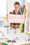 Costurera feliz que muestra el modelo en estudio Foto de archivo libre de regalías