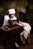Costurera joven con la máquina de coser vieja Foto de archivo libre de regalías