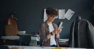 Costurera moderna usando smartphone en la sonrisa que manda un SMS de la pantalla táctil del trabajo almacen de metraje de vídeo