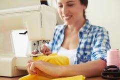 Costurera que cose el vestido amarillo Imagen de archivo
