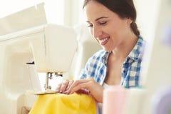 Costurera que cose el vestido amarillo Fotos de archivo libres de regalías
