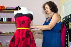 Costurera que hace arreglos en un vestido Foto de archivo