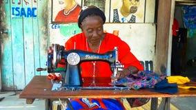 Costurera que hace la ropa en un viejo cantante Sewing Machine foto de archivo
