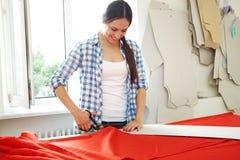 Costurera que trabaja con el modelo y la materia textil roja Imagen de archivo libre de regalías