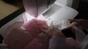 Costurera que trabaja en la máquina de coser metrajes