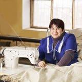 Costurera sonriente en delantal azul Foto de archivo libre de regalías