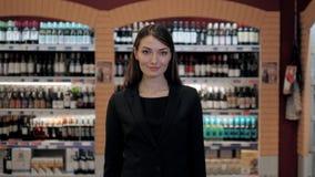 Cosultant na loja de vinho, mulher na loja que escolhe o vinho que concorda a lista ou a informação de verificação no tablet pc Fotografia de Stock Royalty Free