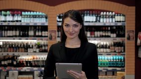 Cosultant in wijnwinkel, Oman in de opslag die wijn kiezen die controlelijst of informatie in tabletcomputer overeenstemmen stock videobeelden