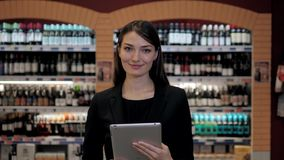 Cosultant in wine shop, woman in the store choosing wine according check list or information in tablet computer. Woman in the store choosing wine according check stock photo