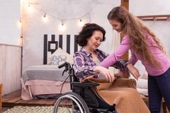 Beautiful girl proposing blanket to crippled woman. Cosy atmosphere. Joyful girl carrying blanket while crippled women taking it Royalty Free Stock Photo