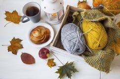 Cosy autumn decor with tea, cinnamon bun, lantern, leaves, knitt Stock Images