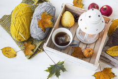 Cosy autumn decor with tea, lantern, fall leaves, knitting wool Royalty Free Stock Photos