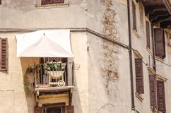 Cosy balcony with a tent and flowers. Hiding from sun. Romantic window with a balcony in Italian style with old facade and wooden shutters Royalty Free Stock Images