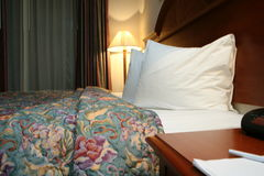 Cosy bedroom. Interior details of comfortable bedroom with bedside table in foreground stock image