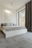 Cosy bedroom with bed huge window Stock Photography