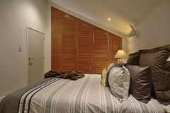 A cosy bedroom. A queen sized bed with pillows and wooden slat blinds over the window Royalty Free Stock Photo