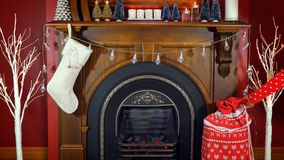 Cosy Christmas holiday decorated mantelpiece and fire place. In red and white theme Stock Photos