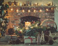 Christmas setting, decorated fireplace, fur tree. Cosy Christmas, presents and decorations on the table in front of fireplace with woodburner, lit up Christmas Royalty Free Stock Image