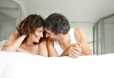 Cosy couple lying on bed in playful mood Royalty Free Stock Photos
