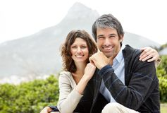 Cosy couple sitting in a park and smiling Royalty Free Stock Images