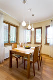 Cosy dining room surrounded by windows. Cosy dining room interior with wooden table surrounded by windows stock photography
