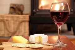 Cosy evening by fire with wine and cheese. Cosy evening at home with red wine, brie or camembert cheese and crackers, in front of a fire in a woodburner or wood Stock Images
