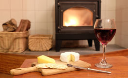 Cosy evening by woodburner fire with wine and cheese. Cosy evening at home with red wine, brie or camembert cheese and crackers, in front of a fire in a Royalty Free Stock Images