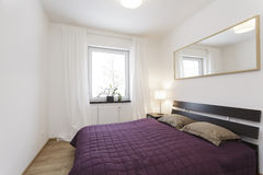 Cosy flat - bedroom. Cosy flat - violet bed in white bedroom Stock Photo