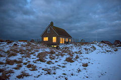 Cosy home in dark. Cosy holiday home in dramatic clouds setting royalty free stock image