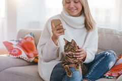 Cosy home family bengal cat girl petting. Cosy home atmosphere. family pet. girl petting her bengal cat while looking at her phone stock photography