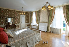 Cosy light bedroom. Cosy spacious bedroom in country cottage royalty free stock images