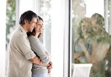 Cosy mature couple standing near a window at home Stock Photography