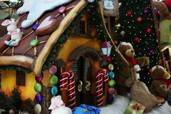 A fantastic gingerbread house full of colorful candies on the background of a Christmas tree stock image