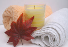 Cosy relaxing bathroom. Warm relaxing bathroom with white and peach towels and cream scented candle with autumnal leaf for a cosy bath or spa treatment Stock Images